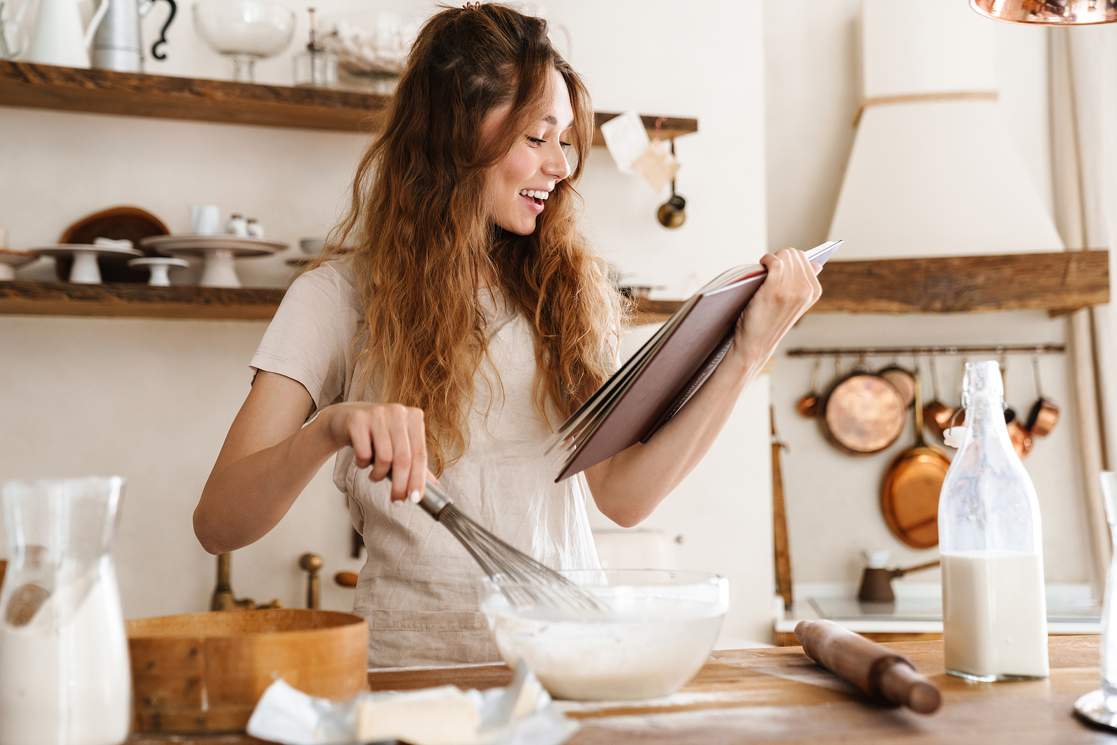 Attractive young cheerful girl baking at the kitchen, making dou